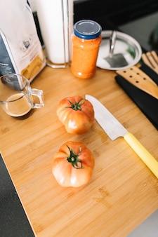 Zwei rote tomaten auf hackendem brett mit scharfem messer