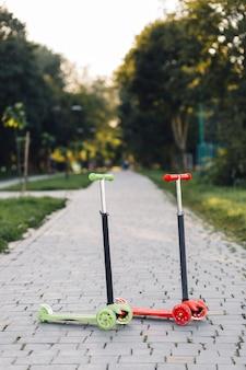 Zwei rote und grüne stoßroller auf dem gehweg im park