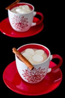 Zwei rote und weiße tasse mit heißer schokolade und marshmallows auf einer platte rot