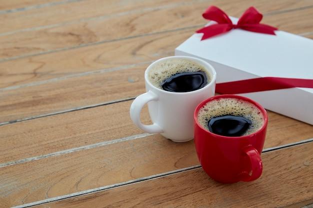 Zwei roter und weißer becherkaffee auf hölzernem