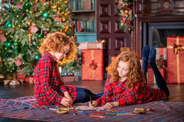 Zwei rothaarige lockige mädchen schreiben einen brief an den weihnachtsmann gegen den weihnachtsbaum und ein dekoriertes zimmer.