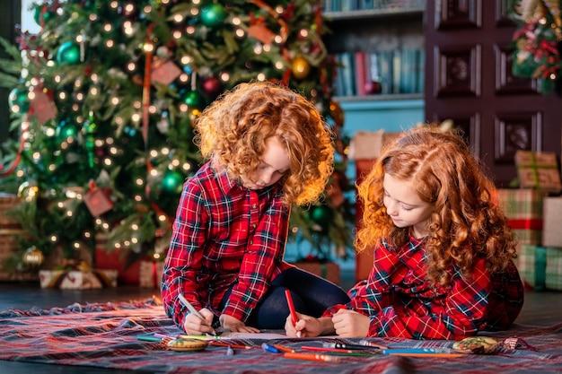 Zwei rothaarige lockige mädchen schreiben vor dem hintergrund eines weihnachtsbaumes und eines dekorierten zimmers einen brief an den weihnachtsmann.