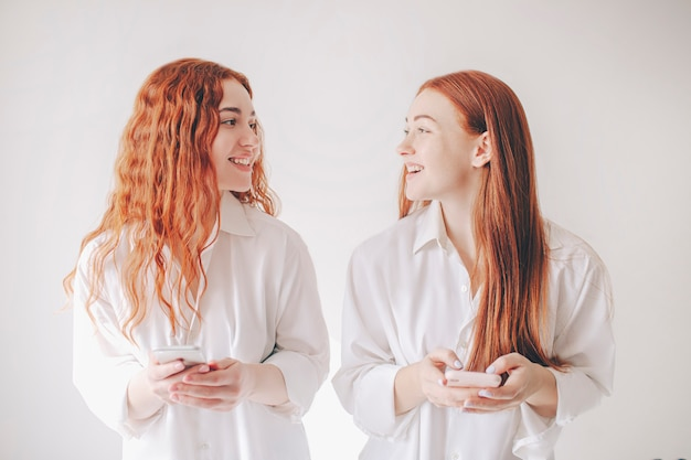Zwei rothaarige schwestern stehen isoliert auf einem weißen hintergrund in geräumigen übergroßen hemden. zwei junge frauen, die süchtig nach sozialen netzwerken sind, verbringen ihre ganze zeit in einem smartphone