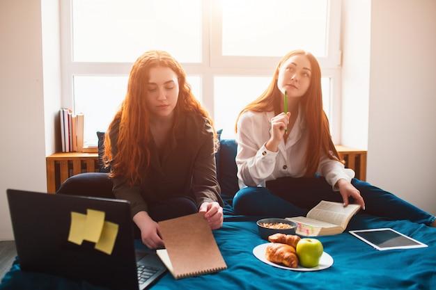 Zwei rothaarige studenten lernen zu hause oder bereiten sich auf prüfungen vor. junge frauen, die hausaufgaben in einem schlafsaalbett nahe dem fenster machen. es gibt notizbücher, lebensmittelbücher, ein tablet und einen laptop sowie dokumente