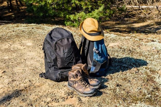 Zwei rucksäcke, touristische stiefel und hut auf einem boden in einem nadelwald