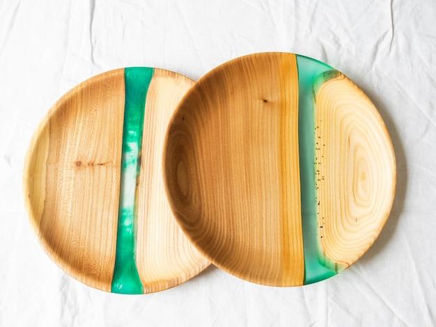 Zwei runde bastelschalen aus holz mit grünen harzeinsätzen