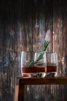 Zwei runde gläser mit einem schuss whisky und einem rosmarinzweig