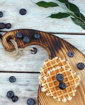 Zwei runde waffeln auf einem holzbrett und blaubeeren