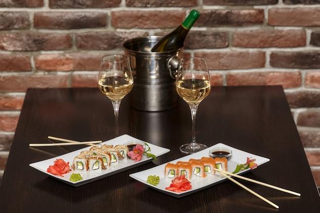 Zwei sätze sushi-rollen mit stäbchen und weingläsern