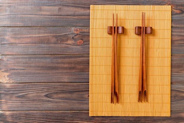 Zwei sätze sushiessstäbchen auf hölzernem bambus
