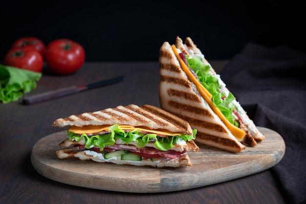 Zwei sandwiches aus scheibe fleisch und käse tomaten zwischen geröstetem brot auf holztisch