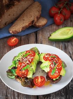 Zwei sandwiches mit frisch gebackenem brot, olivenöl, salat, avocado, sesam und kirschtomaten auf einem weißen teller