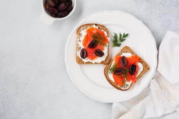 Zwei sandwiches mit geräucherten rosa lachsoliven, kalamata, microgreens und frischkäse auf grauer keramikplatte und trendigem betontisch. traditioneller skandinavischer toast. draufsicht.