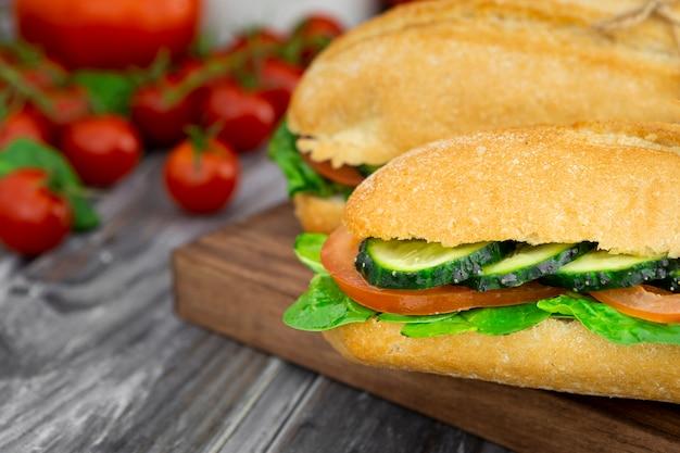 Zwei sandwiches mit gurkenscheiben und defokussierten tomaten