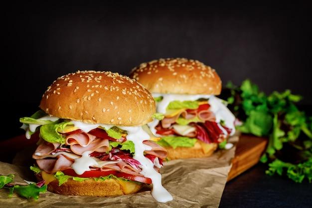 Zwei sandwiches mit schinken, käse, tomaten, salat auf dunkler oberfläche
