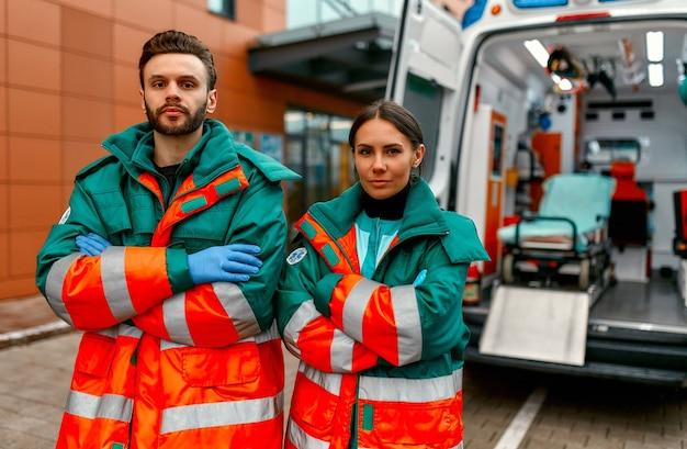 Zwei sanitäter in uniformen stehen mit verschränkten armen vor einer klinik und einem modernen krankenwagen.