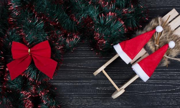 Zwei sankt-hüte auf einem spielzeug weihnachtspferdeschlitten, einem weihnachtsbogen und einem grünen und roten lametta auf schwarzem