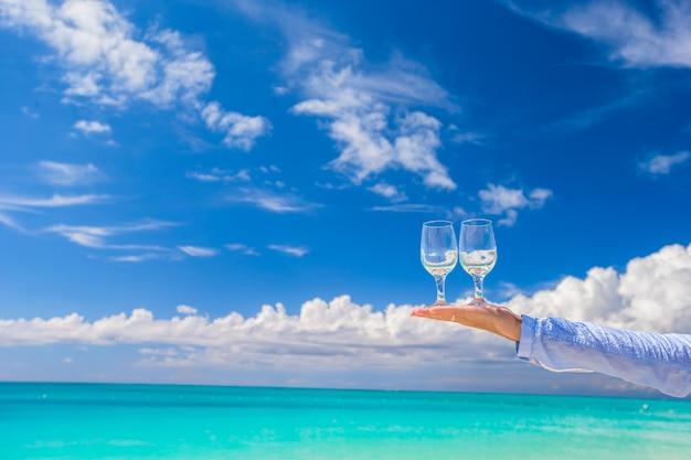 Zwei saubere gläser an der männlichen hand auf hintergrund des blauen himmels