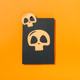 Zwei schädel gelegt auf stück schwarzes papier