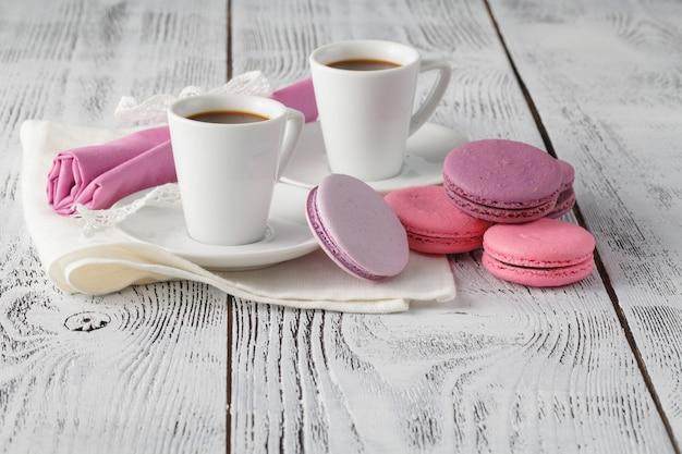 Zwei schalen frisch gebrühter espressokaffee mit makronen auf eine strukturierte holztischoberseite mit copyspace