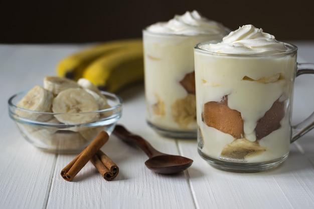 Zwei schalen mit bananenpudding, bananenscheiben und zimt auf einem weißen holztisch.