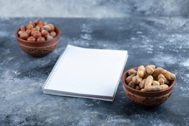 Zwei schalen mit geschälten haselnüssen und erdnüssen mit leerer seite.