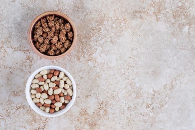 Zwei schalen mit gesunden geschälten erdnüssen, die auf einen steinhintergrund gelegt werden.