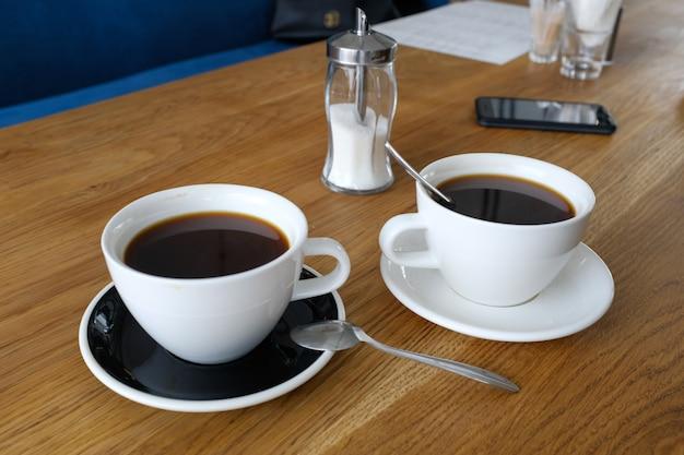 Zwei schalen schwarzes cofffee auf hölzerner tabelle, morgenkaffee.