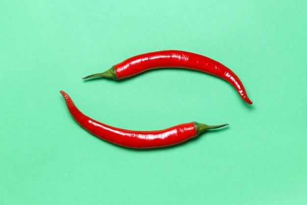 Zwei scharfe rote chilischoten bilden yin yang ein symbol auf grün. flache lage.