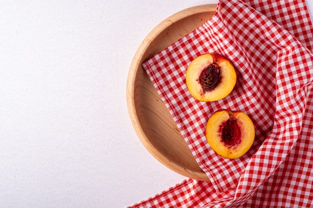 Zwei scheibe pfirsichnektarinenfrucht mit samen in der hölzernen platte mit roter karierter tischdecke auf weißem hintergrund, kopienraum, draufsicht, ebenenlage