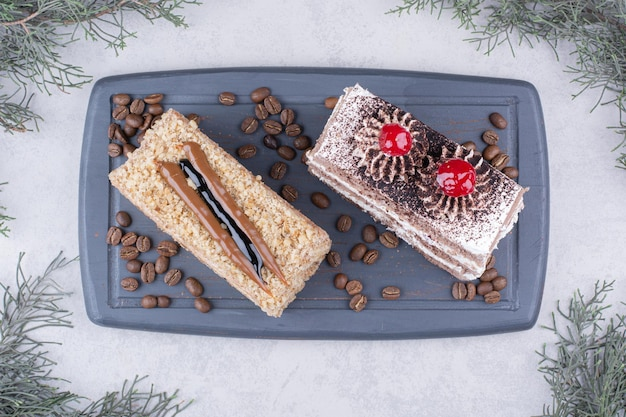 Zwei scheiben kuchen auf dunklem teller mit kaffeebohnen.