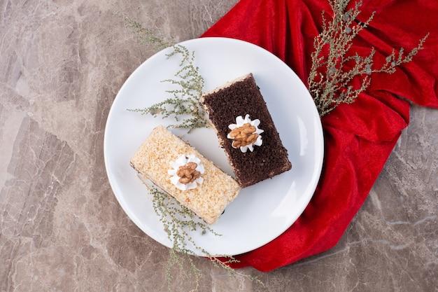 Zwei scheiben kuchen auf weißem teller mit roter tischdecke.