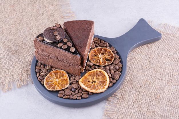Zwei scheiben schokoladenkuchen mit kaffeebohnen und orangenscheiben. foto in hoher qualität