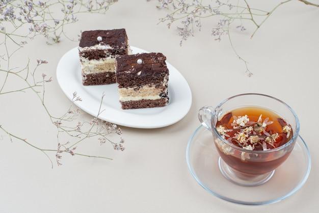 Zwei scheiben tiramisu-kuchen und eine tasse tee auf weißer oberfläche