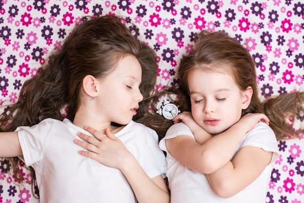 Zwei schlafende mädchen und ein weißer wecker