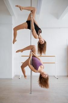Zwei schlanke frauen beim pole-dance-training. professionelle tänzerinnen, die im fitnessstudio trainieren, pole dance