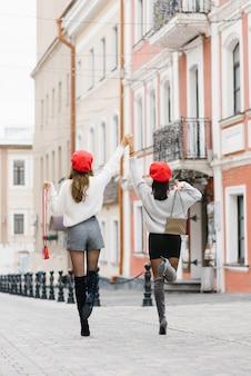 Zwei schlanke freundinnen in einem kurzen rock und kurzen hosen, rote baskenmützen und mit taschen in den händen, die hände hielten, die sich erhoben. sie genießen ihr glück und ihre freundschaft