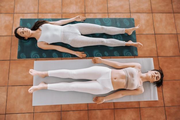 Zwei schlanke junge frauen, die barfuß auf dem rücken auf der matte in corpse yoga-position liegen und sich entspannen.