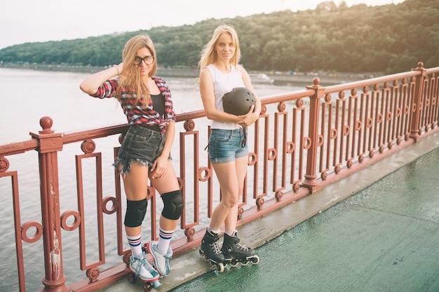 Zwei schlanke und sexy junge frauen und rollschuhe. eine frau hat inline-skates und die andere quad-skates. mädchen reiten in den strahlen der sonne.