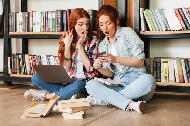 Zwei schockierte teenager-mädchen sitzen auf einem boden