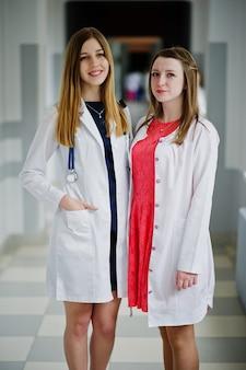 Zwei schöne ärztinnen oder medizinische arbeitskräfte in den weißen mänteln, die im krankenhaus aufwerfen.