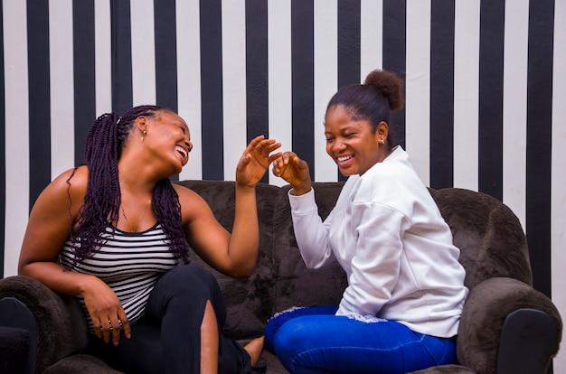 Zwei schöne afrikanische damen, die sich glücklich fühlen, während sie diskutieren.