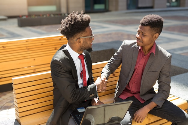 Zwei schöne afrikanische leute auf einer bank mit einem laptop in einem handschlag