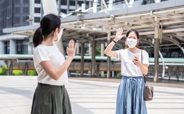 Zwei schöne asiatische frauen grüßen mit einer kollegin, die jedes mal außerhalb des hauses eine medizinische einweg-gesichtsmaske trägt, als neuen normalen trend und selbstschutz gegen covid19-infektionen.