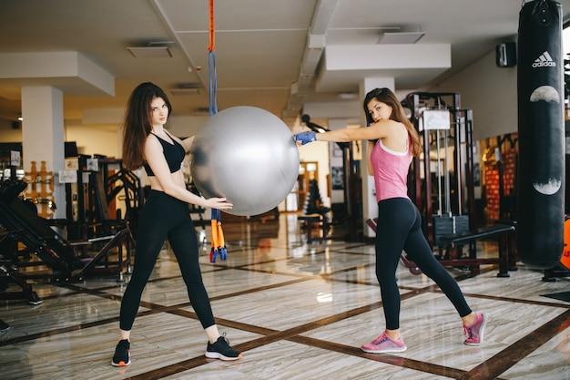 Zwei schöne athletische mädchen nehmen an der turnhalle teil