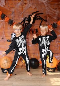 Zwei schöne blonde jungen, die skelettkostüme tragen und auf der halloween-party tanzen