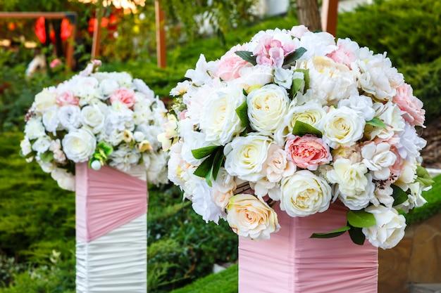Zwei schöne blumensträuße mit rosen im freien. hochzeitszeremonie dekoration.
