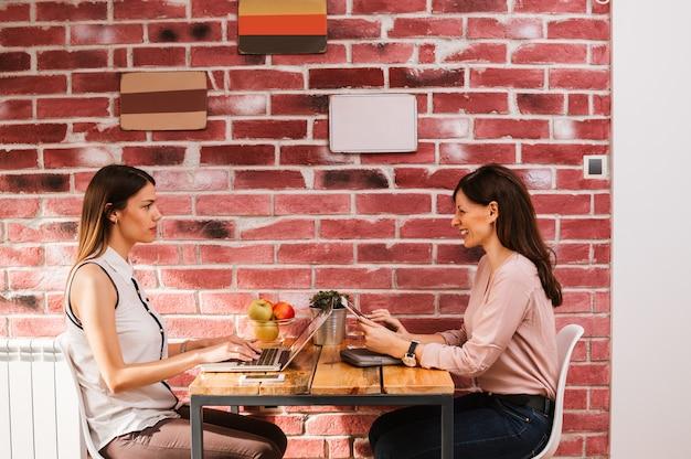 Zwei schöne damen, die in einer kaffeestube arbeiten.