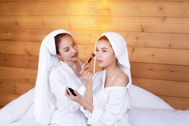 Zwei schöne damen, die weißes hemd tragen und auf bett sitzen, bilden zusammen, entspannen sich zeit