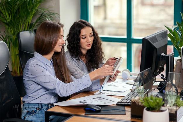 Zwei schöne designerin im büro, die mit farbmustern arbeitet. kreative menschen oder werbegeschäftskonzept.